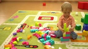 Szczęśliwy preschool żartuje bawić się z wielo- coloured blokami przy salowym boiskiem Dziecko sporta aktywność zbiory wideo