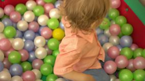 Szczęśliwy preschool berbeć bawić się w wielo- coloured balowym basenie Przedszkole zbiory wideo