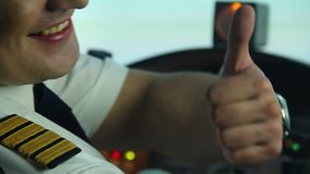 Szczęśliwy profesjonalisty pilot w kokpicie pokazuje aprobaty podpisuje, cieszący się jego pracę zbiory