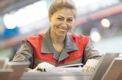 Szczęśliwy przemysłowy żeński pracownik na manufaktura warsztata tle Fotografia Royalty Free