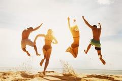 Szczęśliwy przyjaciela zmierzchu plaży bieg skok Obrazy Stock