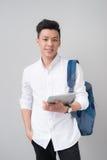 Szczęśliwy przypadkowy azjatykci męski uczeń używa pastylka komputer odizolowywał o obrazy stock