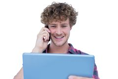 Szczęśliwy przystojny mężczyzna mienia pastylki komputer i mieć rozmowę telefonicza Obrazy Stock