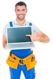 Szczęśliwy repairman wskazuje przy laptopem Obrazy Stock