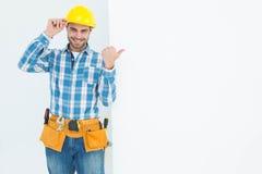 Szczęśliwy repairman wskazuje w kierunku pustego billboardu Obrazy Stock