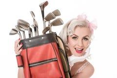 Szczęśliwy retro dziewczyny zerkanie out od behind czerwonej golfowej torby, odosobnionej Fotografia Stock