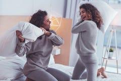 Szczęśliwy rodzeństw czuć rozochocony podczas gdy mieć poduszki bitwę fotografia stock