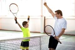 Szczęśliwy rodzic i dziecko ma zabawę na tenisowym sądzie Zdjęcia Royalty Free