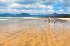 Szczęśliwy rodzina bieg szeroką piasek plażą Obrazy Stock
