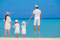 Szczęśliwy rodzina składająca się z czterech osób na biel plaży zdjęcie stock