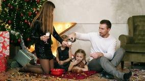 Szczęśliwy rodzina składająca się z czterech osób siedzi choinką i je czekoladowych ciastka Uśmiechnięty ojciec nalewa szampana zbiory