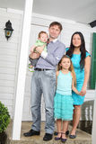 Szczęśliwy rodzina składająca się z czterech osób stojak na ganeczku nowa chałupa. zdjęcia royalty free