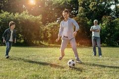 Szczęśliwy rodzinny bawić się futbol outdoors Obrazy Stock