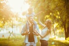 Szczęśliwy rodzinny bawić się w natury późnego popołudnia świetle słonecznym w spadku, lato Matka, ojciec i córka bawić się na tr zdjęcie stock