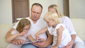 Szczęśliwy rodzinny bawić się wraz z laptopem i cyfrową pastylką w domu Ojcuje, matka i dwa dzieciaka siedzi na kanapie i zbiory wideo