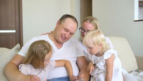 Szczęśliwy rodzinny bawić się wraz z laptopem i cyfrową pastylką w domu Ojcuje, matka i dwa dzieciaka siedzi na kanapie i zbiory