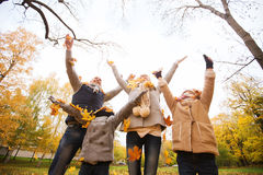 Szczęśliwy rodzinny bawić się z jesień liśćmi w parku Fotografia Royalty Free