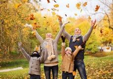 Szczęśliwy rodzinny bawić się z jesień liśćmi w parku Fotografia Stock