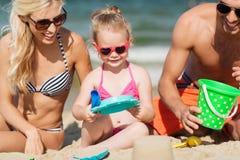 Szczęśliwy rodzinny bawić się z piaskiem bawi się na plaży Zdjęcie Royalty Free