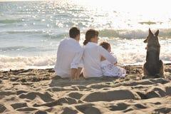 Szczęśliwy rodzinny bawić się z psem na plaży Zdjęcia Stock