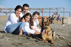 Szczęśliwy rodzinny bawić się z psem na plaży Obrazy Stock