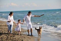 Szczęśliwy rodzinny bawić się z psem na plaży Fotografia Stock