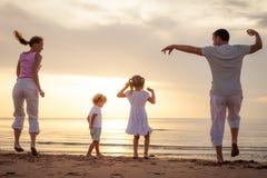 Szczęśliwy rodzinny doskakiwanie na plaży fotografia stock