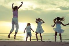 Szczęśliwy rodzinny doskakiwanie na plaży zdjęcia royalty free