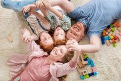Szczęśliwy rodzinny lying on the beach na podłoga, duży rodzinny portreta pojęcie Zdjęcia Royalty Free