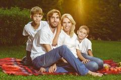 Szczęśliwy rodzinny lying on the beach na trawie w lecie piknik Zdjęcia Stock