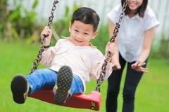 Szczęśliwy rodzinny mieć zabawę na huśtawkowej przejażdżce przy ogródem Zdjęcie Stock