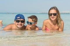 Szczęśliwy rodzinny mieć zabawę na tropikalnej biel plaży Matka, ojciec, śliczny syn Pozytywne ludzkie emocje, uczucia, radość Śm Obraz Royalty Free