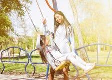 Szczęśliwy rodzinny mieć zabawy przejażdżkę na huśtawce dziewczynka z kędzierzawym włosy i jego matką uśmiecha się each inny spad Zdjęcie Stock