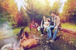 Szczęśliwy rodzinny obsiadanie na ławce przy obozu ogieniem Zdjęcia Stock