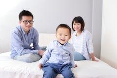Szczęśliwy rodzinny obsiadanie na białym łóżku Zdjęcia Stock