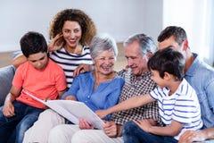 Szczęśliwy rodzinny obsiadanie na kanapie i patrzeć album fotograficznego obrazy royalty free