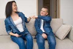 Szczęśliwy rodzinny obsiadanie na kanapie i używać cyfrową pastylkę w domu Zdjęcie Stock