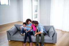 Szczęśliwy rodzinny obsiadanie na kanapie wpólnie zdjęcie stock