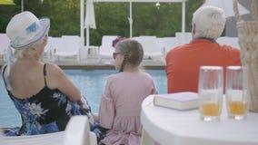 Szczęśliwy rodzinny obsiadanie na krawędzi basenu, tylny widok Babcia, dziad i wnuk relaksuje przy wodą, zbiory