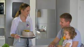 Szczęśliwy rodzinny obsiadanie w kuchni, mum dekoruje owoc tort zbiory wideo