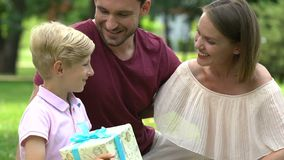 Szczęśliwy rodzinny odświętność synów urodziny, przedstawia ładnego prezent, kochający rodzice zbiory