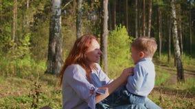 Szczęśliwy rodzinny odpoczywać na gazonie Matka z czułością i miłością bawić się z jej dzieckiem synów śmiechy, on zabawę Szczęśl zbiory