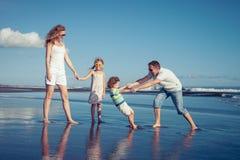 Szczęśliwy rodzinny odprowadzenie na plaży przy dnia czasem Obrazy Royalty Free