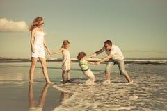 Szczęśliwy rodzinny odprowadzenie na plaży przy dnia czasem Obrazy Stock