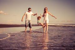 Szczęśliwy rodzinny odprowadzenie na plaży przy dnia czasem Fotografia Stock