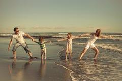 Szczęśliwy rodzinny odprowadzenie na plaży przy dnia czasem Zdjęcia Royalty Free