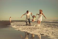 Szczęśliwy rodzinny odprowadzenie na plaży przy dnia czasem Zdjęcia Stock
