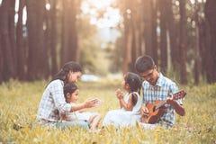 Szczęśliwy rodzinny ojciec bawić się gitarę z matką i dzieckiem Zdjęcia Stock