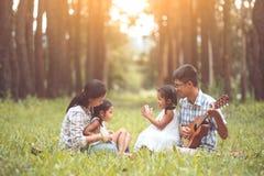 Szczęśliwy rodzinny ojciec bawić się gitarę z matką i dzieckiem Zdjęcie Royalty Free