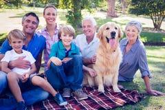 Szczęśliwy rodzinny ono uśmiecha się przy kamerą z ich psem Fotografia Royalty Free